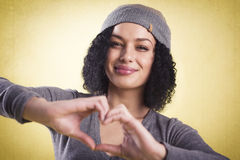 Beautiful woman smiling and showing a heart. stock photos