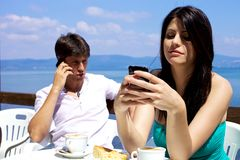 Beautiful woman smiling while texting on cellphone Royalty Free Stock Photography