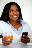 Beautiful woman smiling and using a cellphone Stock Photos
