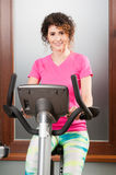 Beautiful woman smiling and using stationary bicycle Royalty Free Stock Image
