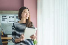 Beautiful woman smiling while using tablet computer Royalty Free Stock Image