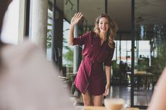 Beautiful woman smiling and waving her hands to her friends Royalty Free Stock Photo