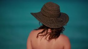 Beautiful woman smiling, wearing beach straw hat in front of ocean stock footage