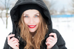 Beautiful woman smiling wearing hood and winter clothes Royalty Free Stock Photos