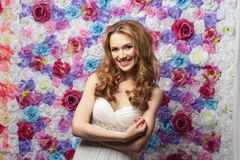 Beautiful woman smiling, wearing a wedding dress on a background of flowers. Emotion shyness. Beautiful woman smiling, wearing a wedding dress, on a background Stock Photo