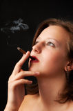 Beautiful woman smokes a cigarette. In the dark Royalty Free Stock Photo