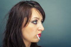 Beautiful woman smokes a cigarette Royalty Free Stock Photo