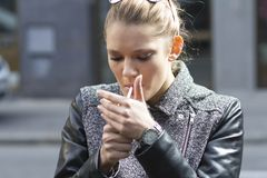 Beautiful woman smokes a cigarette on the street Stock Images