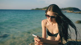 Beautiful woman sms texting using app on smart phone at beach sunset during vacation stock footage