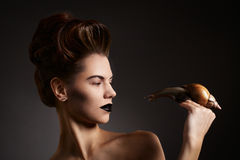 Beautiful woman with snail with black eyes and lips. Fashion. Go. Woman with snail with black eyes and lips in Gothic Halloween image royalty free stock photography