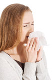 Beautiful woman sneezing, holding a tissue. Stock Images