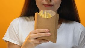Beautiful woman sniffing and proposing french fries in carton box, takeaway. Stock footage stock video