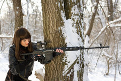 Beautiful woman with a sniper rifle. Beautiful young woman with a sniper rifle near the tree Royalty Free Stock Photos