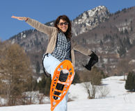 Beautiful woman with snowshoes in winter in snowy mountain Stock Images