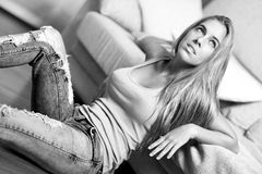 Beautiful woman in a sofa. Beautiful young woman in a sofa of a livingroom of a house Royalty Free Stock Photo