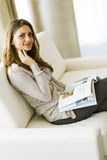 Beautiful woman on a sofa reading a paper in the living room Stock Photos