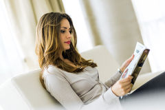 Beautiful woman on a sofa reading a paper in the living room Royalty Free Stock Images