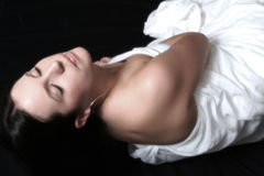 Beautiful Woman In Soft Focus. Colour portrait of female lying on floor draped in white sheet. Soft focus effect Royalty Free Stock Images