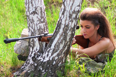 Beautiful woman soldier with a sniper rifle royalty free stock images
