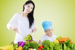 Beautiful woman and son make salad Stock Photos