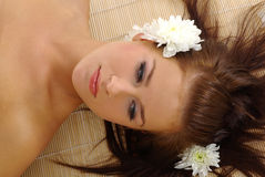Beautiful woman after spa. Portrait of Fresh and Beautiful woman laying on bamboo mat around flowers and taking spa treatment royalty free stock image