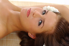 Beautiful woman after spa. Portrait of Fresh and Beautiful woman laying on bamboo mat around flowers stock image