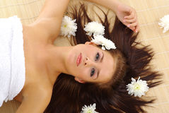 Beautiful woman after spa. Portrait of Fresh and Beautiful woman laying on bamboo mat around flowers royalty free stock photos