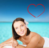 Beautiful woman in spa salon. Health and beauty, resort and relaxation concept - beautiful woman with flower in her hair in spa salon lying on the massage desk royalty free stock image