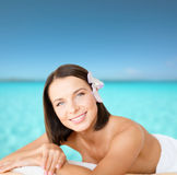 Beautiful woman in spa salon. Health and beauty, resort and relaxation concept - beautiful woman with flower in her hair in spa salon lying on the massage desk stock photo