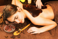 Beautiful woman in spa salon having chocolate therapy procedure Stock Images