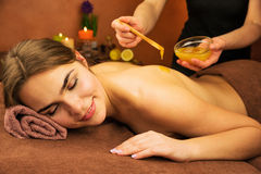 Beautiful woman in spa salon having spa therapy honey procedure Stock Image