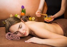 Beautiful woman in spa salon having spa therapy honey procedure Stock Photography