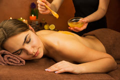 Beautiful woman in spa salon having spa therapy honey procedure Royalty Free Stock Photos
