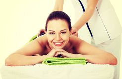 Beautiful woman on spa salon having stone massage. Royalty Free Stock Photography