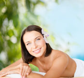 Beautiful woman in spa salon. Health and beauty, resort and relaxation concept - beautiful woman with flower in her hair in spa salon lying on the massage desk royalty free stock images