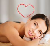 Beautiful woman in spa salon with hot stones Stock Images