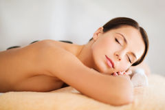 Beautiful woman in spa salon with hot stones Stock Image