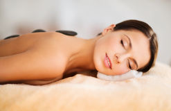 Beautiful woman in spa salon with hot stones Stock Photos