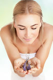 Beautiful woman at spa salon. Portrait of a woman at spa beauty salon, holds in hands lavender and sea salt, enjoying aromatherapy herbal anti-stress treatment royalty free stock image
