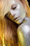 Sparkles on Woman Face and body. Beautiful Woman with Sparkles. Golden Girl with Art Make-Up in Color Light. Fashion blonde Model with Colorful Makeup and hair royalty free stock photos