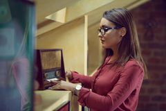 Beautiful woman with specs listen to an old radio. Young woman wearing eyeglasses listen to a vintage radio Royalty Free Stock Photography