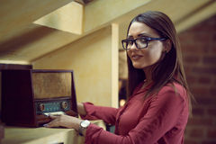 Beautiful woman with specs listen to an old radio. Young woman wearing eyeglasses listen to a vintage radio Royalty Free Stock Image