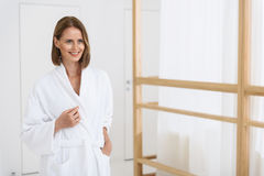 Beautiful woman spending time in spa centre. Getting pampered at spa. Cropped shot of smiling attractive woman in white bathrobe relaxing day spa while arriving Royalty Free Stock Images
