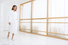 Beautiful woman spending time in spa centre. I am ready for my spa treatment. Shot of beautiful woman spending her weekend in spa, walking along corridor and Royalty Free Stock Image