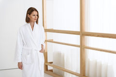 Beautiful woman spending time in spa centre. On way to relaxation. Beautiful woman arriving at spa hall and holding her hand in pocket of white bathrobe Stock Photos