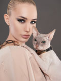 Beautiful woman with Sphynx cat. Beautiful blomd woman with Sphynx cat.beauty make-up model girl with kitty royalty free stock image
