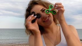 Beautiful    woman with a fidget spinner steel vacation on the sea. Beautiful woman with a spinner fidget on the sea vacation steel stock video