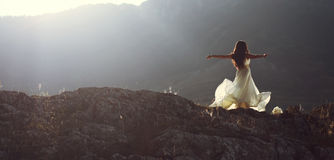 Beautiful woman spinning with arms open. Panorama of young beautiful woman bride in long white dress stretching arms spinning and dancing on mountain
