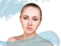 Beautiful woman in splashes of clear blue water. Royalty Free Stock Images
