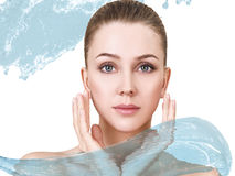 Beautiful woman in splashes of clear blue water. Royalty Free Stock Photo
